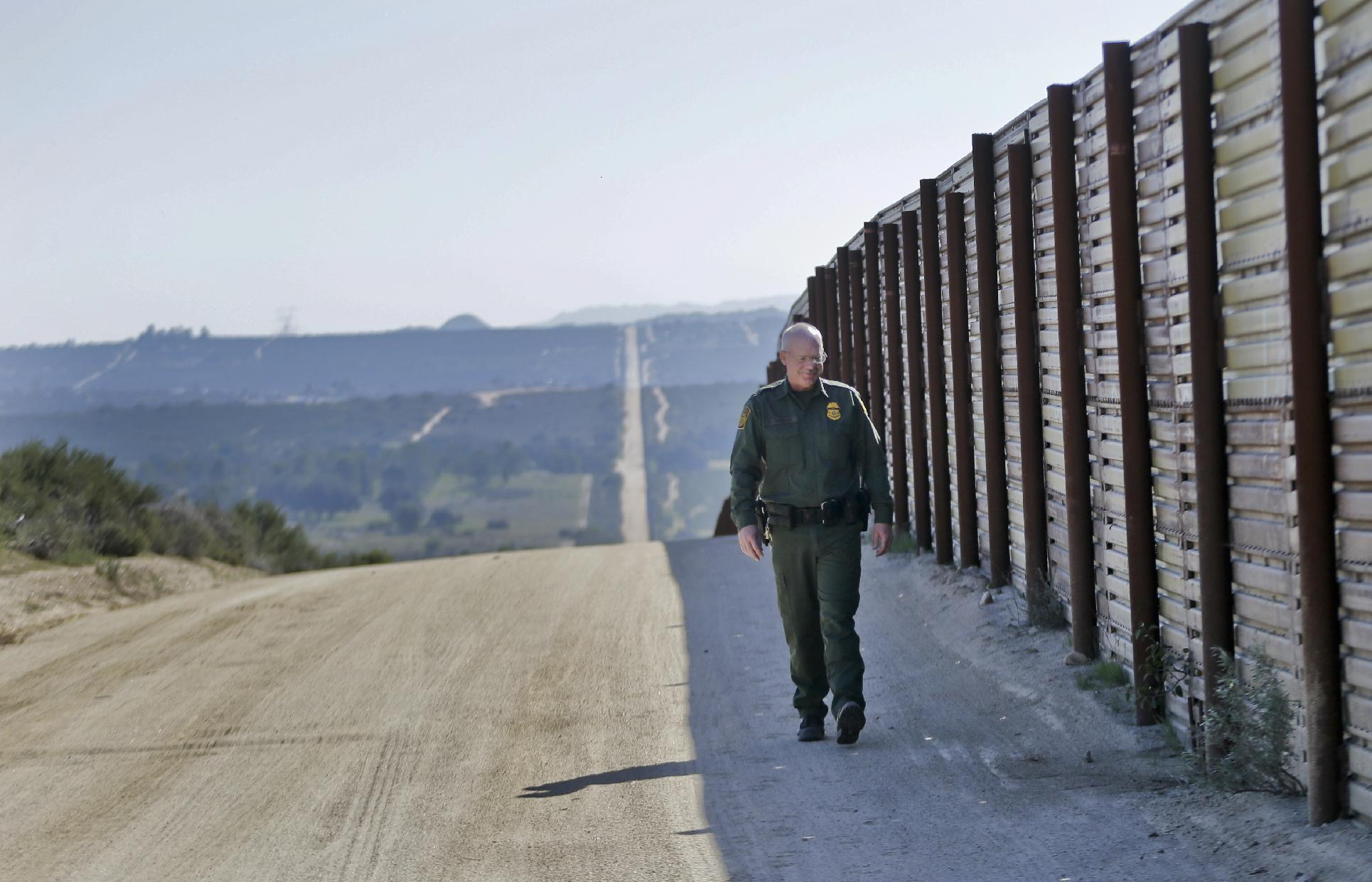"""In this Monday, March 25, 2013 photo, Border Patrol agent Richard Gordon, a 23-year veteran of the agency, walks the border fence in the Boulevard area east of San Diego looking for signs that reveal movement of illegal immigrants in the rugged, mountainous terrain in Boulevard, Calif. For the past 16 years, Gordon has been one of the top """"sign-cutters"""" or trackers in the Border Patrol. (AP Photo/Lenny Ignelzi)"""