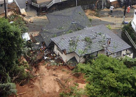 Rescue workers are seen next to houses damaged by a landslide following heavy rain in Kitakyushu, southwestern Japan, in this photo taken by Kyodo July 6, 2018. Mandatory credit Kyodo/via REUTERS