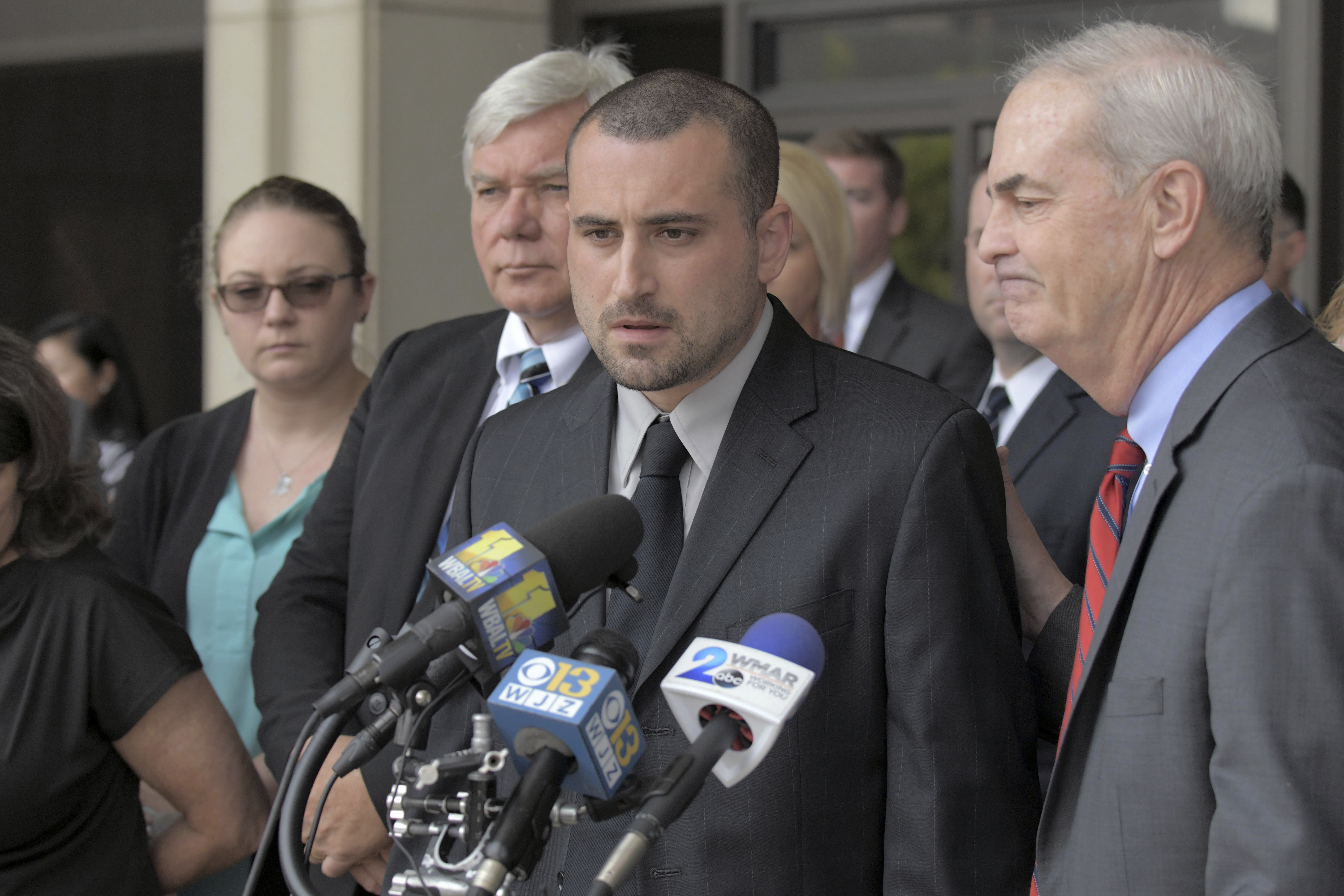 Widower Tim Caprio speaks, between father in-law Garry Sorrells, left, and Baltimore County State's Attorney Scott Shellenberger following the life sentence meted out for 17-year-old Dawnta Harris at Baltimore County Circuit Court Wednesday, Aug. 21, 2019, in Towson, Md. Harris was tried as an adult earlier this year and convicted of felony murder in the slaying of Baltimore County police Officer Amy Caprio. (Karl Merton Ferron/The Baltimore Sun via AP)