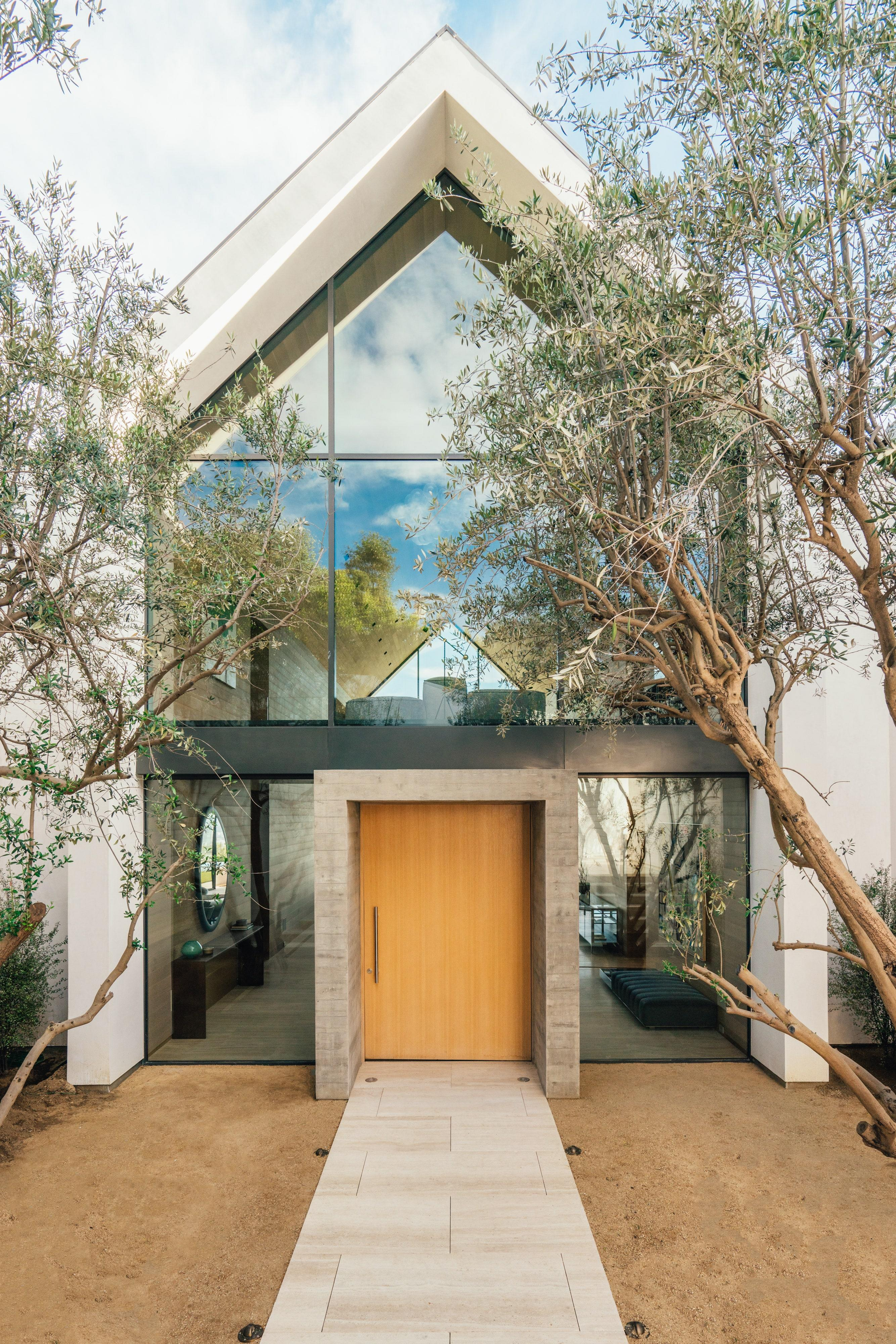 """""""The house is tall and the space was tight, so creating a meaningful entry experience was the biggest challenge,"""" says Allsbrook. """"Arriving at the house, you descend into a small courtyard that has a more intimate scale. We framed the door in a concrete cube flanked by two mature olive trees. These elements bring a human scale to the house and precede the drama of the interior height."""""""