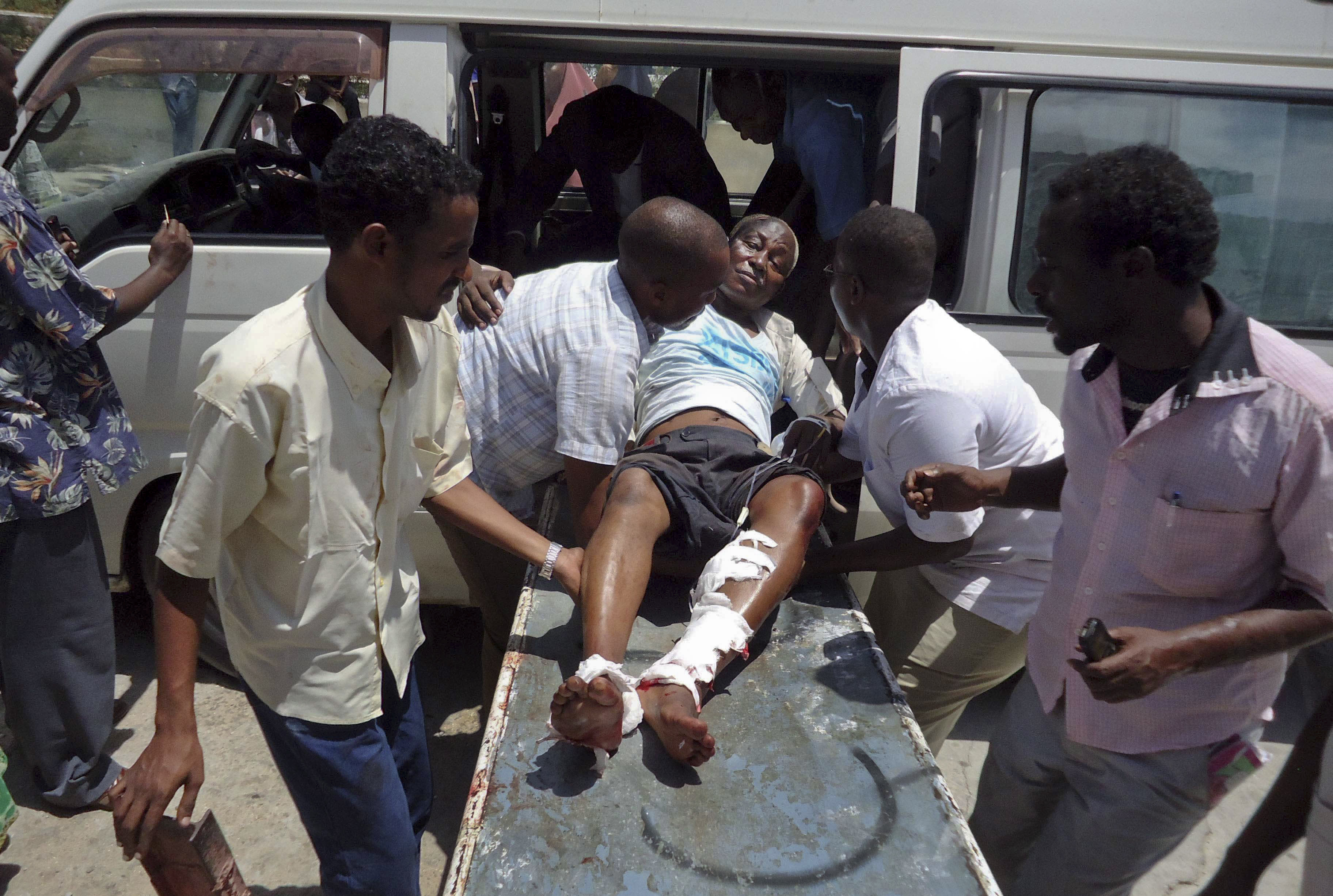 Medical personnel help a man wounded in a blast at the Somali National Theater in Mogadishu, Somalia Wednesday, April 4, 2012. An explosion Wednesday at a ceremony at Somalia's national theater killed at least 10 people including two top sports officials in an attack by an Islamist group on a site that symbolized the city's attempt to rise from two decades of war. (AP Photo/Farah Abdi Warsameh)
