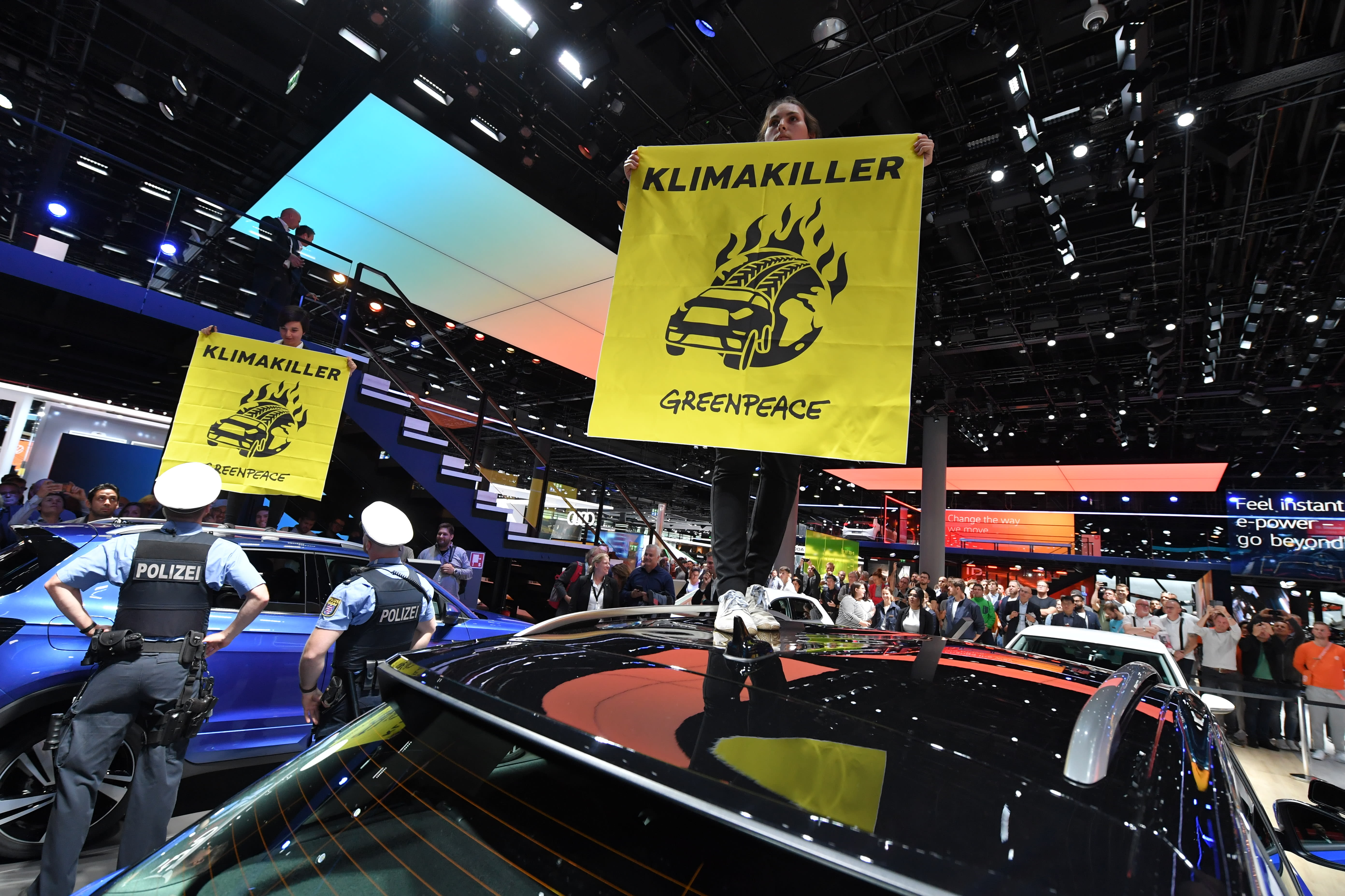 Greenpeace activists protest at the IAA Auto Show in Frankfurt, Germany, Thursday, Sept. 12, 2019. The banner is reading 'Klimakiller-Climate killer'. (Boris Roessler/dpa via AP)