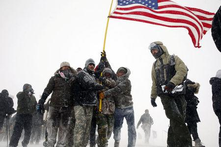 "Veterans join activists in a march to Backwater Bridge just outside of the Oceti Sakowin camp during a snow fall as ""water protectors"" continue to demonstrate against plans to pass the Dakota Access pipeline adjacent to the Standing Rock Indian Reservation"