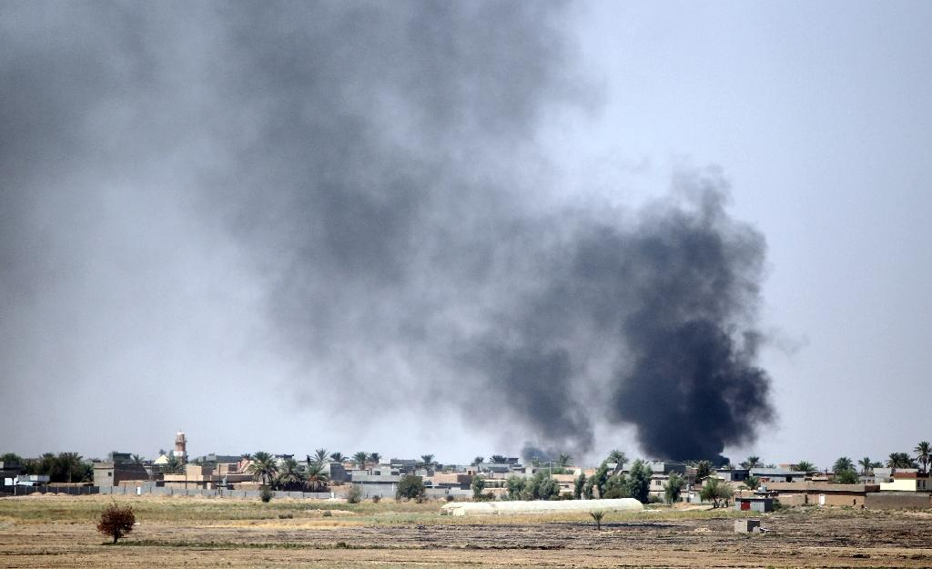 Smoke rises in the distance after clashes in the village of Yakanja, near Tuz Khurmatu, on September 1, 2014 (AFP Photo/Ali Al-Saadi)
