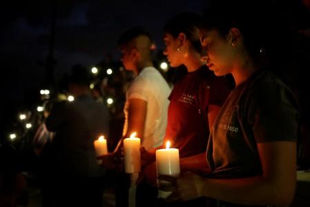 Mourners taking part in a vigil at El Paso High School after a mass shooting at a Walmart store in El Paso