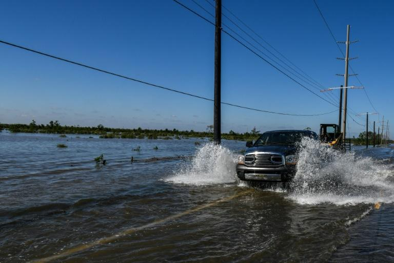 A truck drives through floodwaters in Lake Charles, Louisiana on October 10, 2020 following Hurricane Delta