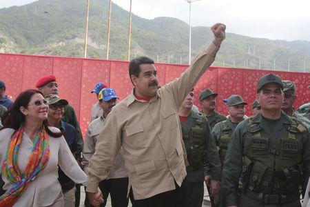 Venezuela's President Nicolas Maduro (C) greets supporters as he arrives to a military parade, next to his wife and deputy of Venezuela's United Socialist Party (PSUV) Cilia Flores (L) and Venezuela's Defense Minister Vladimir Padrino Lopez (R) in La Guaira, Venezuela May 21, 2016. Miraflores Palace/Handout via REUTERS