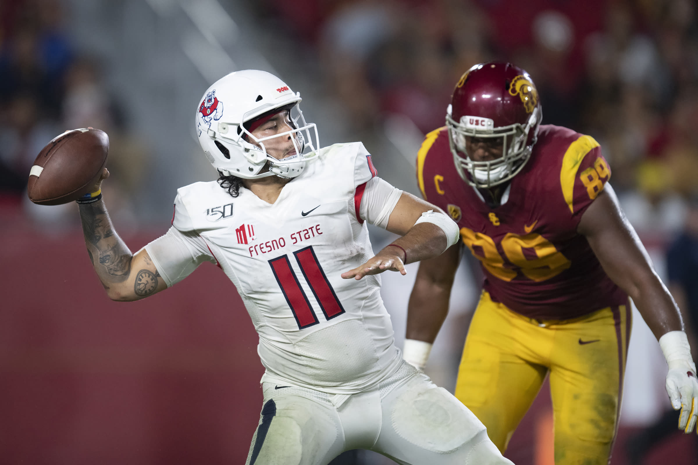 FILE - In this Sept. 31, 2019, file photo, Fresno State quarterback Jorge Reyna, left, looks to throw a pass as Southern California USC Trojans defensive lineman Christian Rector approaches during an NCAA college football game in Los Angeles. The NCAA's Board of Governors is urging Gov. Gavin Newsom not to sign a California bill that would allow college athletes to receive money for their names, likenesses or images. In a six-paragraph letter to Newsom, the board said the bill would give California schools an unfair recruiting advantage. As a result, the letter says, the NCAA would declare those schools ineligible for its events. (AP Photo/Kyusung Gong, File)