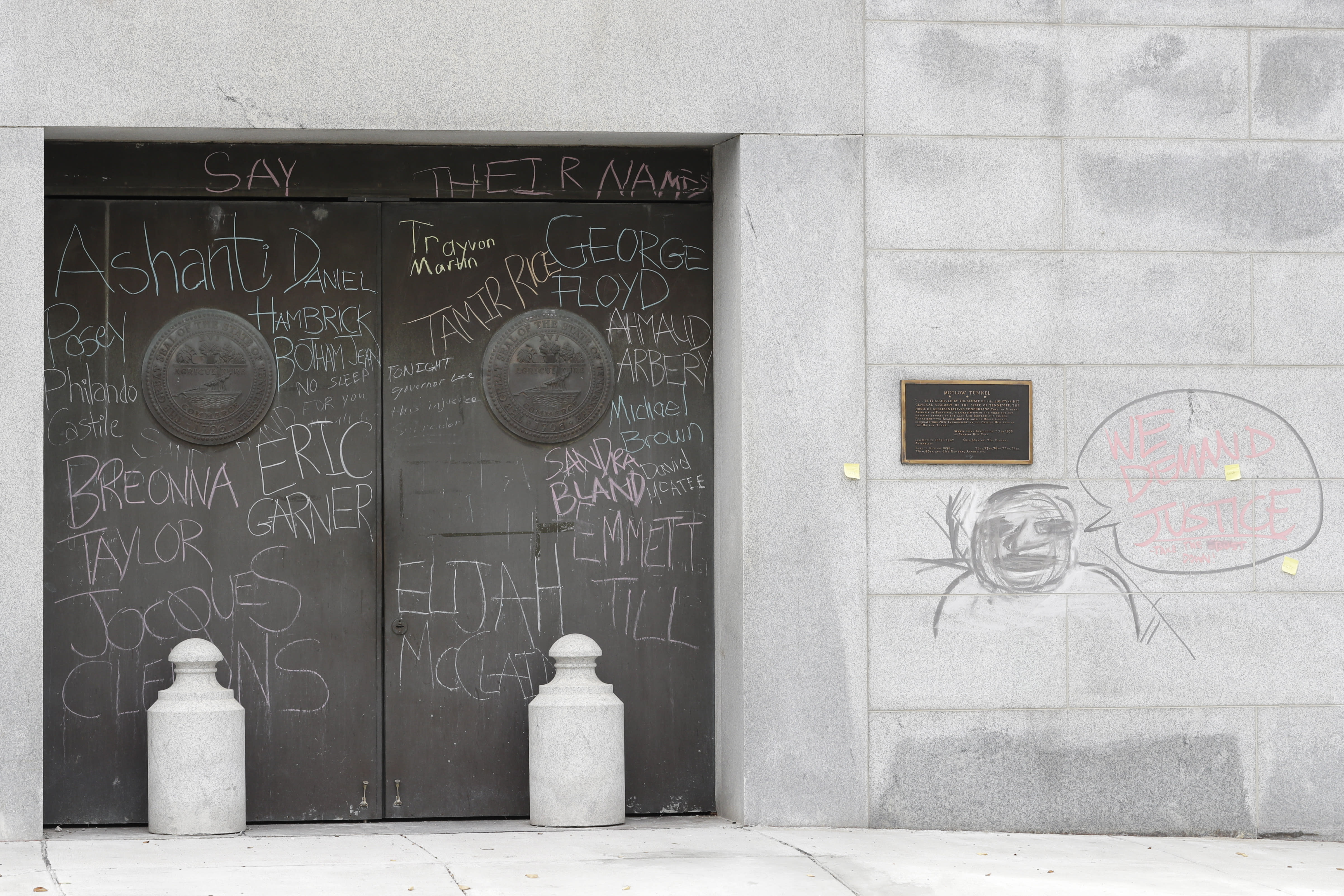 """Graffiti from demonstrators protesting social injustice is left on doors and a wall at the state capitol Wednesday, July 1, 2020, in Nashville, Tenn. Tennessee's newest law, a wide range of crimes commonly associated with protests will see a big bump in penalties and fines, but the most contentious element focuses on escalated penalties for """"illegal camping"""" on state property from a misdemeanor to a felony, punishable by up to six years in prison. (AP Photo/Mark Humphrey)"""
