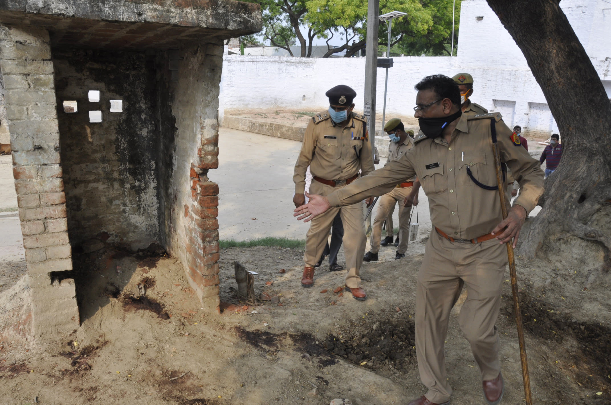 Policemen inspect the scene of an ambush in Kanpur, India, Friday, July 3, 2020. A gang of criminals ambushed and fired on police who had come to arrest them in a northern Indian village early Friday, killing eight of the officers, a government official said. The criminals blocked a road with excavators and fired on the police officers from rooftops, said Awanish Awasthi, an Uttar Pradesh state government spokesman. Five officers were injured and the assailants fled before police reinforcements could reach the area, Awasthi said. (AP Photo)
