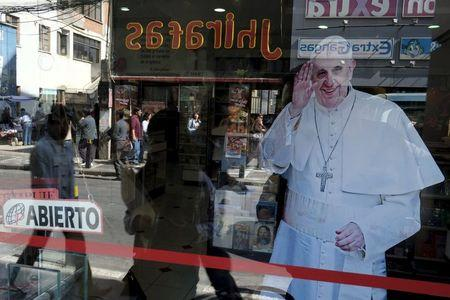 Pedestrians are reflected in a shop window which shows an image of Pope Francis in La Paz, July 1, 2015. REUTERS/David Mercado