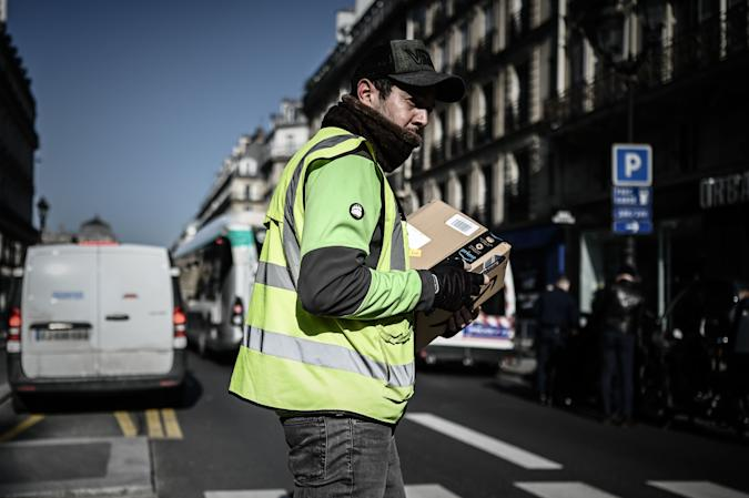 A man crosses a street as he delivers an Amazon parcel in Paris on March 19, 2020, on the third day of a strict lockdown in France to stop the spread of COVID-19, caused by the novel coronavirus. (Photo by PHILIPPE LOPEZ / AFP) (Photo by PHILIPPE LOPEZ/AFP via Getty Images)