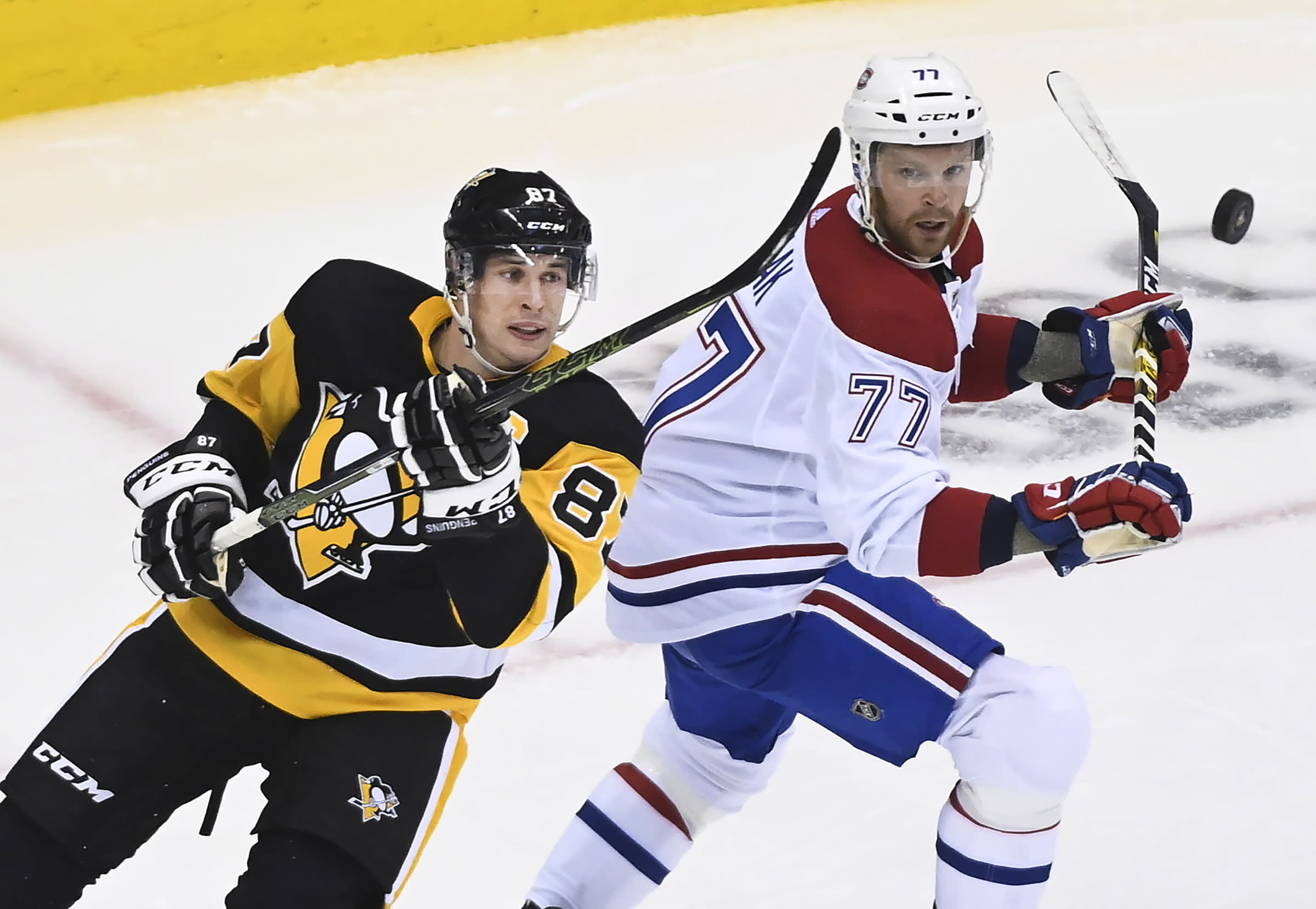 Pittsburgh Penguins center Sidney Crosby (87) eyes the puck next to Montreal Canadiens defenseman Brett Kulak (77) during the third period of an NHL hockey playoff game in Toronto, Saturday, Aug. 1, 2020. (Nathan Denette/The Canadian Press via AP)