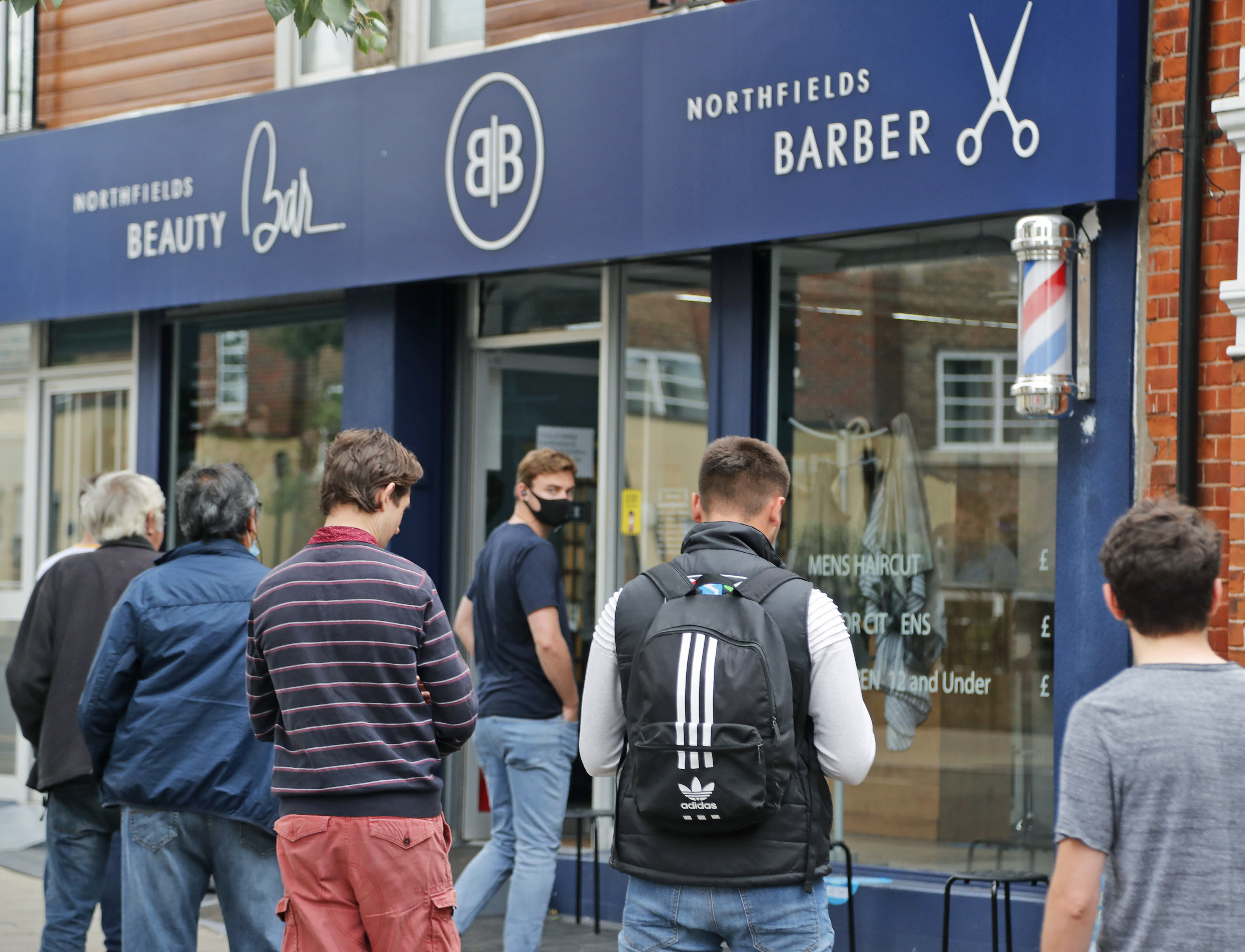 People queue outside Northfields Barber as it opens for the first time after the COVID-19 lockdown in London, Saturday, July 4, 2020. England is embarking on perhaps its biggest lockdown easing yet as pubs and restaurants have the right to reopen for the first time in more than three months. In addition to the reopening of much of the hospitality sector, couples can tie the knot once again, while many of those who have had enough of their lockdown hair can finally get a trim. (AP Photo/Frank Augstein)