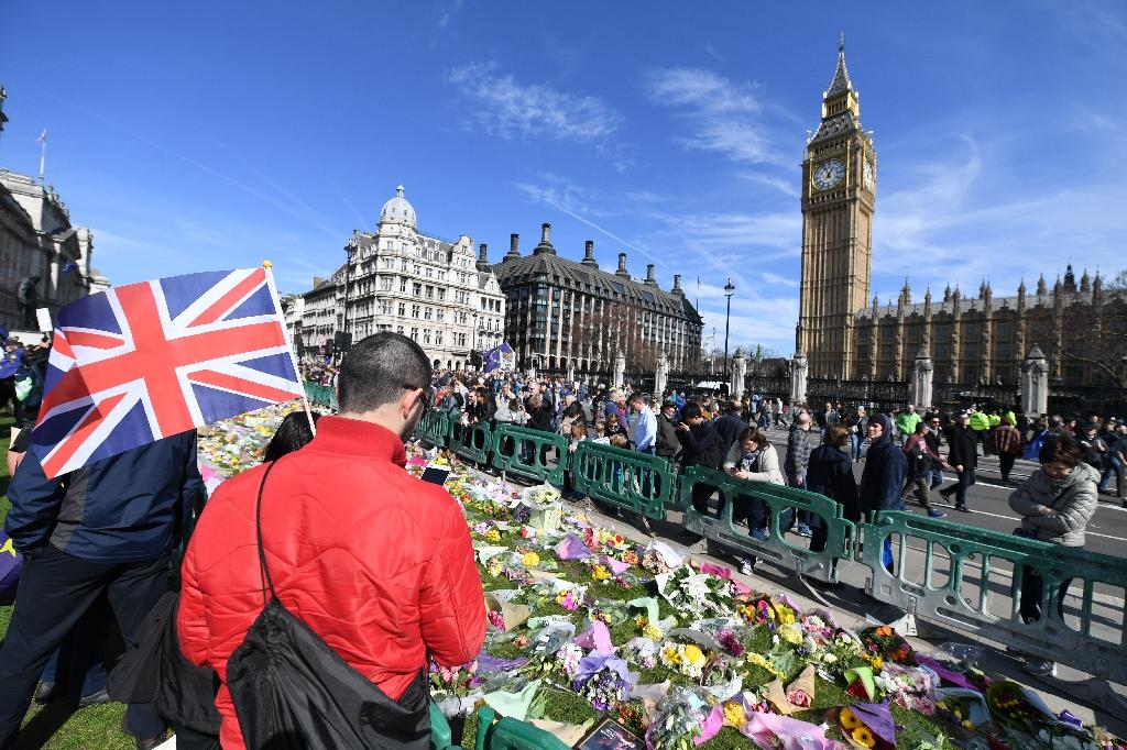 Floral tributes left in honour of the victims of the London terror attack on March 22, are pictured in Parliament Square in Westminster, central London on March 25, 2017 during an anti-Brexit march