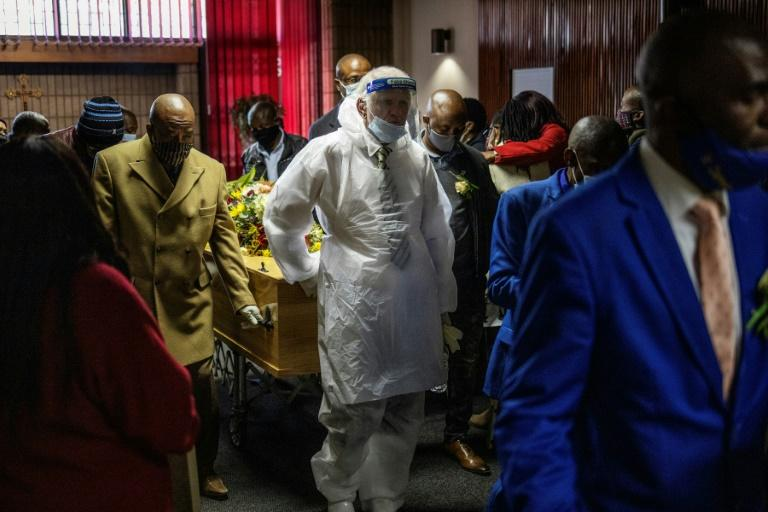 An undertaker wears a protective suit for a funeral in Johannesburg. South Africa has the highest numbers of diagnosed infections in Africa (AFP Photo/Michele Spatari)
