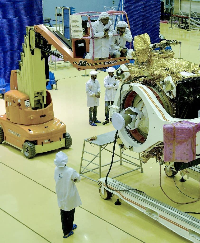 Scientists work on the orbiter vehicle of India's first moon lander (AFP Photo/MANJUNATH KIRAN)