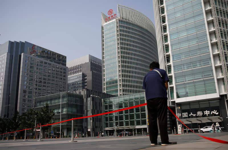 Worker wearing a face mask following the outbreak of the coronavirus disease (COVID-19) sets up a line at a square at the Financial Street area in Beijing