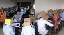 Schüler schreiben Prüfung mit Kartons auf dem Kopf