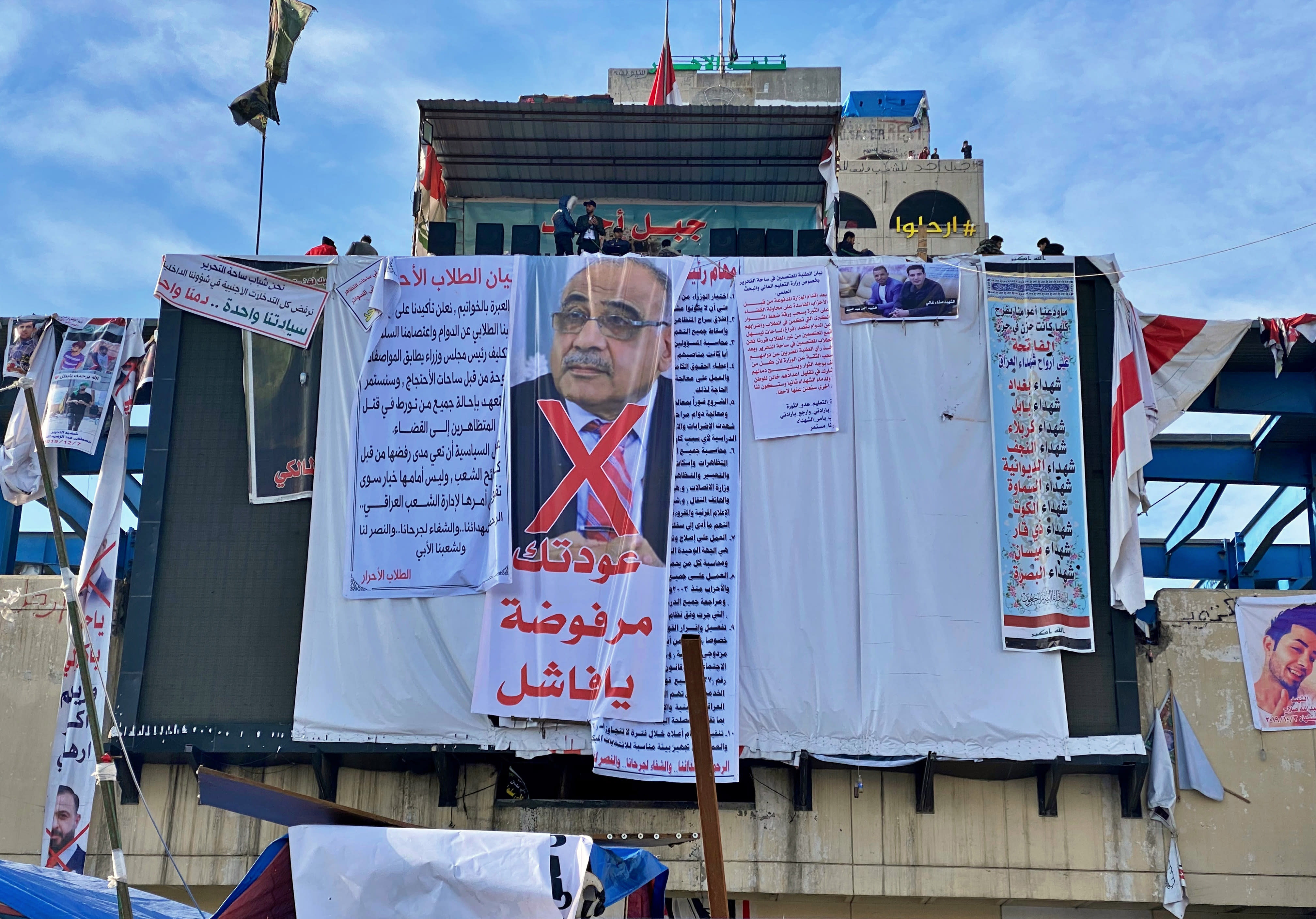 """In this Monday, Jan. 13, 2020 photo, a poster with a defaced picture of Iraqi acting Prime Minister Adil Abdul-Mahdi, and Arabic that reads, """"Your return is rejected, loser,"""" hangs in Tahrir Square, in Baghdad, Iraq. Mass protests by young Iraqis against their country's ruling elite helped force the resignation of the prime minister, but with the focus now turning to the conflict between the United States and Iran, demonstrators fear the momentum is being drawn away from their goals. (AP Photo/Khalid Mohammed)"""