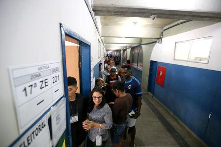 Brazilians stand in line to cast their votes in the presidential election at the Ayrton Senna school, in Rio de Janeiro, Brazil October 7, 2018. REUTERS/Sergio Moraes