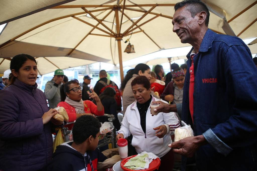 Venezuelan migrants get food from volunteers upon their arrival at a bus terminal in the north of Lima, Peru; the EU has announced a 35 million euro aid package for Venezuelans both inside the country and in neighbouring countries