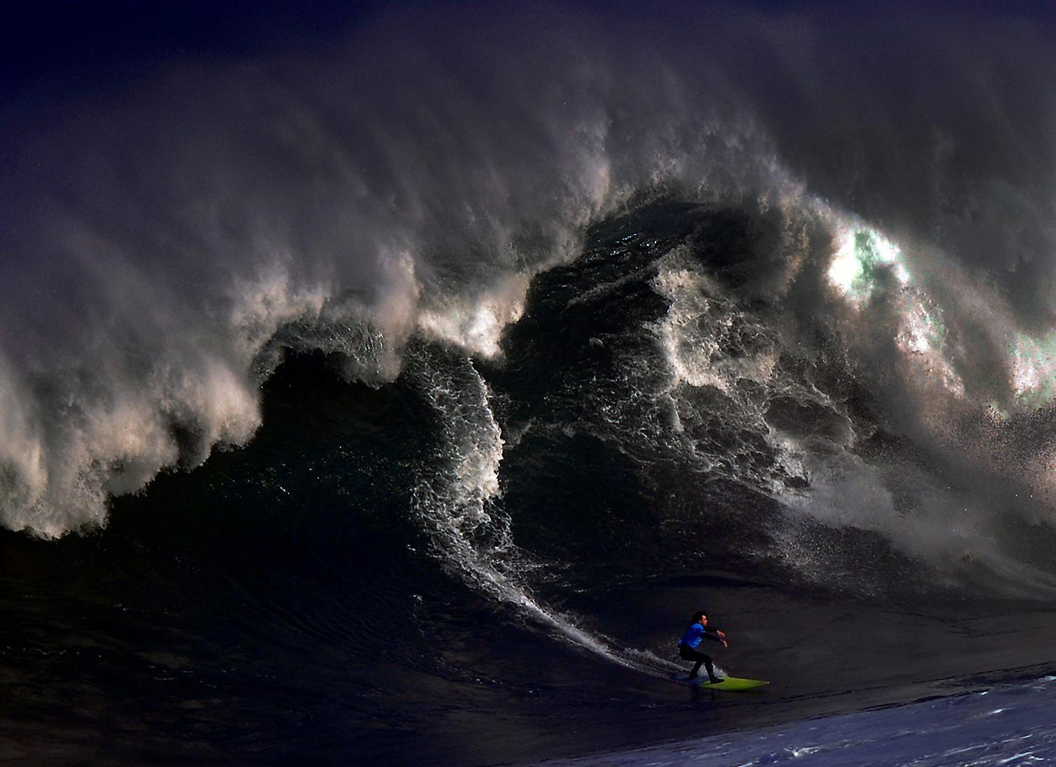 <p>A surfer rides a large wave at El Bocal during the Vaca Gigante (Big Cow) giant wave surf competition in Santander, northern Spain Dec. 17, 2016. (Photo: Vincent West/Reuters) </p>