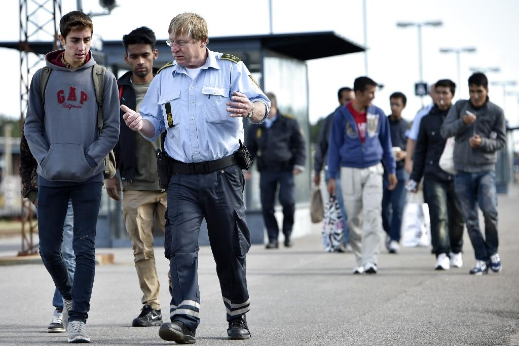 Refugees, mainly from Syria, speak with a Danish policeman after arriving in Rodby, southern Denmark, from Germany on September 7, 2015 (AFP Photo/Jens Noergaard Larsen)