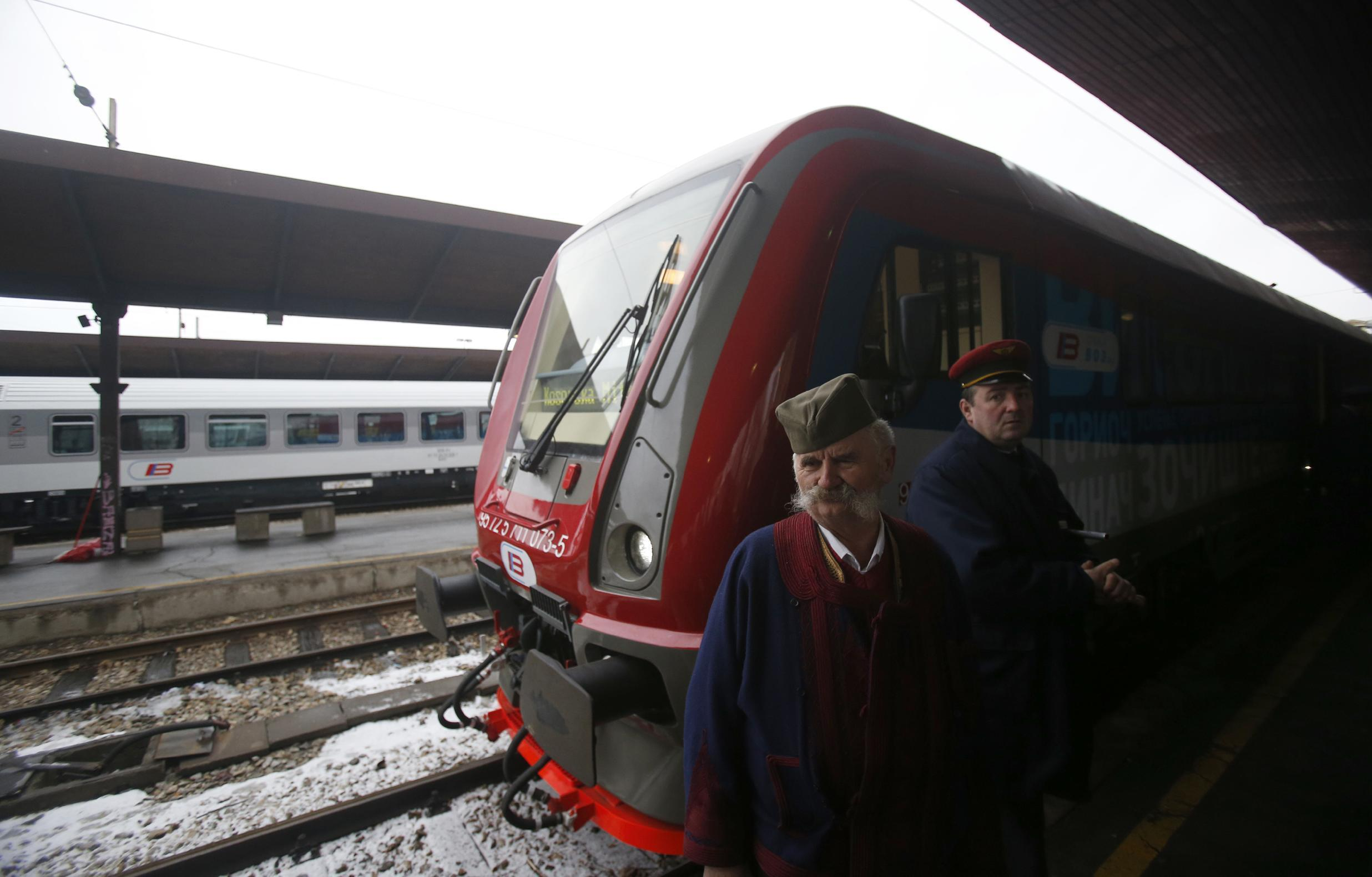 """A man dressed in Serbian national costume passes by a train decorated with """"Kosovo is Serbian"""" inscribed in twenty world languages before it departs from Belgrade to Mitrovica, Kosovo at Belgrade's railway station, Serbia, Saturday, Jan. 14, 2017. Serbia has launched a railway link to Serb-dominated northern Kosovo despite protests from authorities in Pristina who described the move as a provocation and an aggressive violation of Kosovo's sovereignty. (AP Photo/Darko Vojinovic)"""