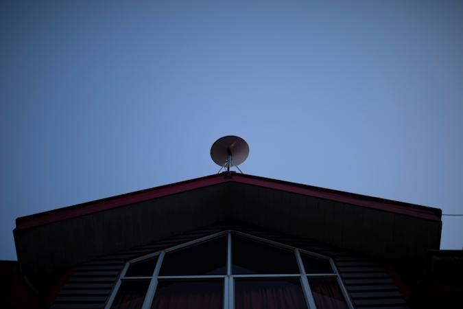 """The Starlink antenna is seen on the roof of the John F Kennedy School located in the village of Sotomo, outside the town of Cochamo, Los Lagos region, Chile, August 7, 2021. Picture taken August 7, 2021. Sotomo is one of two places in Chile to be chosen for a pilot project run by billionaire Elon Musk to receive free internet for a year. The signal is received via a satellite dish installed on the school's roof, which transmits through a Wi-Fi device. REUTERS/Pablo Sanhueza         SEARCH """"SOTOMO SANHUEZA"""" FOR THIS STORY. SEARCH """"WIDER IMAGE"""" FOR ALL STORIES."""
