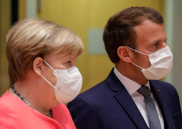 Germany's Chancellor Angela Merkel (L) and France's President Emmanuel Macron were described as looking annoyed after they left a late night meeting with the Netherlands' Prime Minister Charles Rutte (AFP Photo/STEPHANIE LECOCQ)