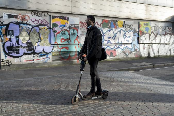 Warring a face covering on his chin, a commuter rides an eScooter past the graffiti on the exterior of a former office property in during the third lockdown of the Coronavirus pandemic, on 26th February 2021, in London, England. (Photo by Richard Baker / In Pictures via Getty Images)