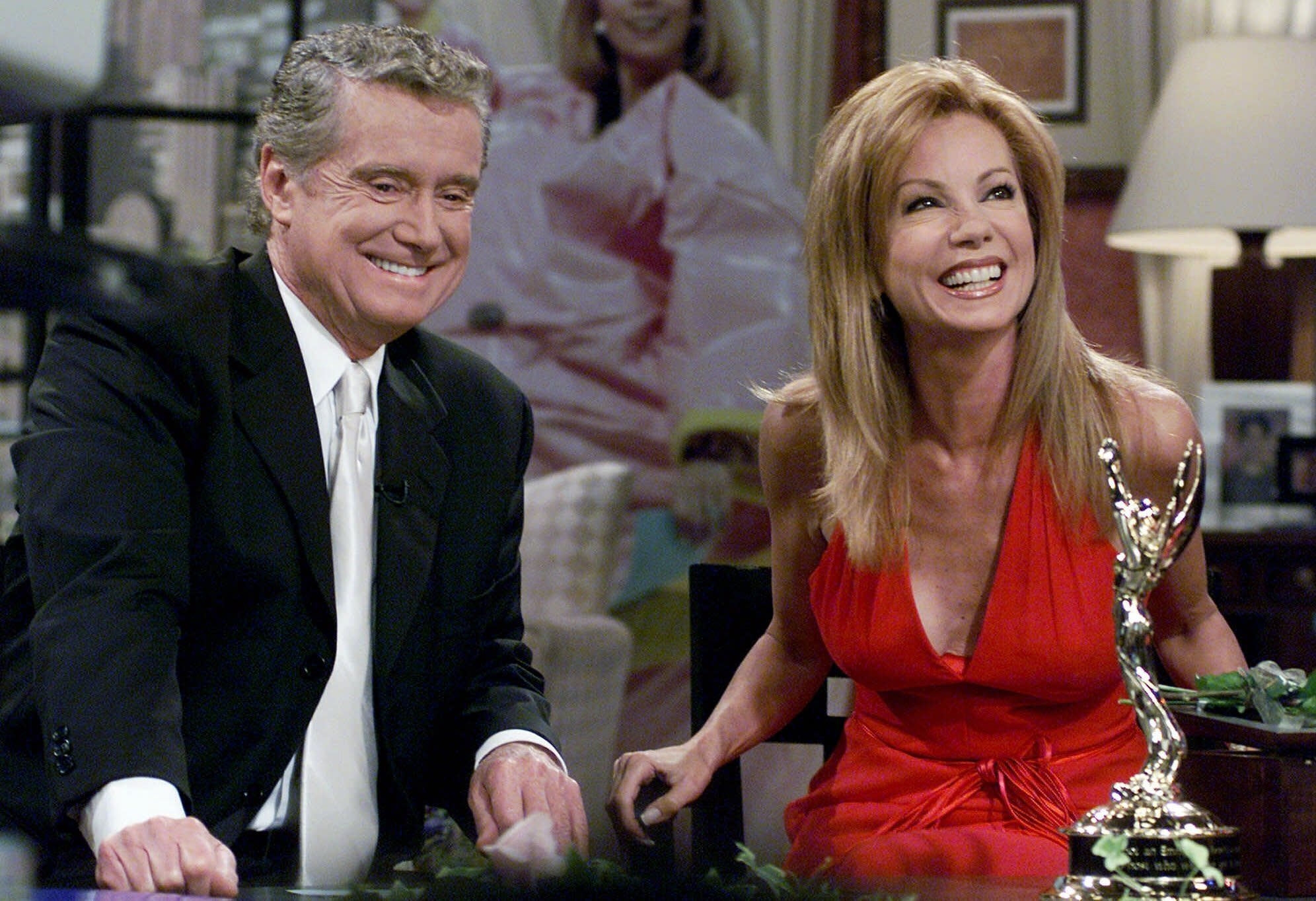 """FILE - In this July 28, 2000 file photo, Kathie Lee Gifford and co-host Regis Philbin reminisce during her last appearance on the show, in New York. Philbin, the genial host who shared his life with television viewers over morning coffee for decades and helped himself and some fans strike it rich with the game show """"Who Wants to Be a Millionaire,"""" has died on Friday, July 24, 2020. (AP Photo/Richard Drew)"""