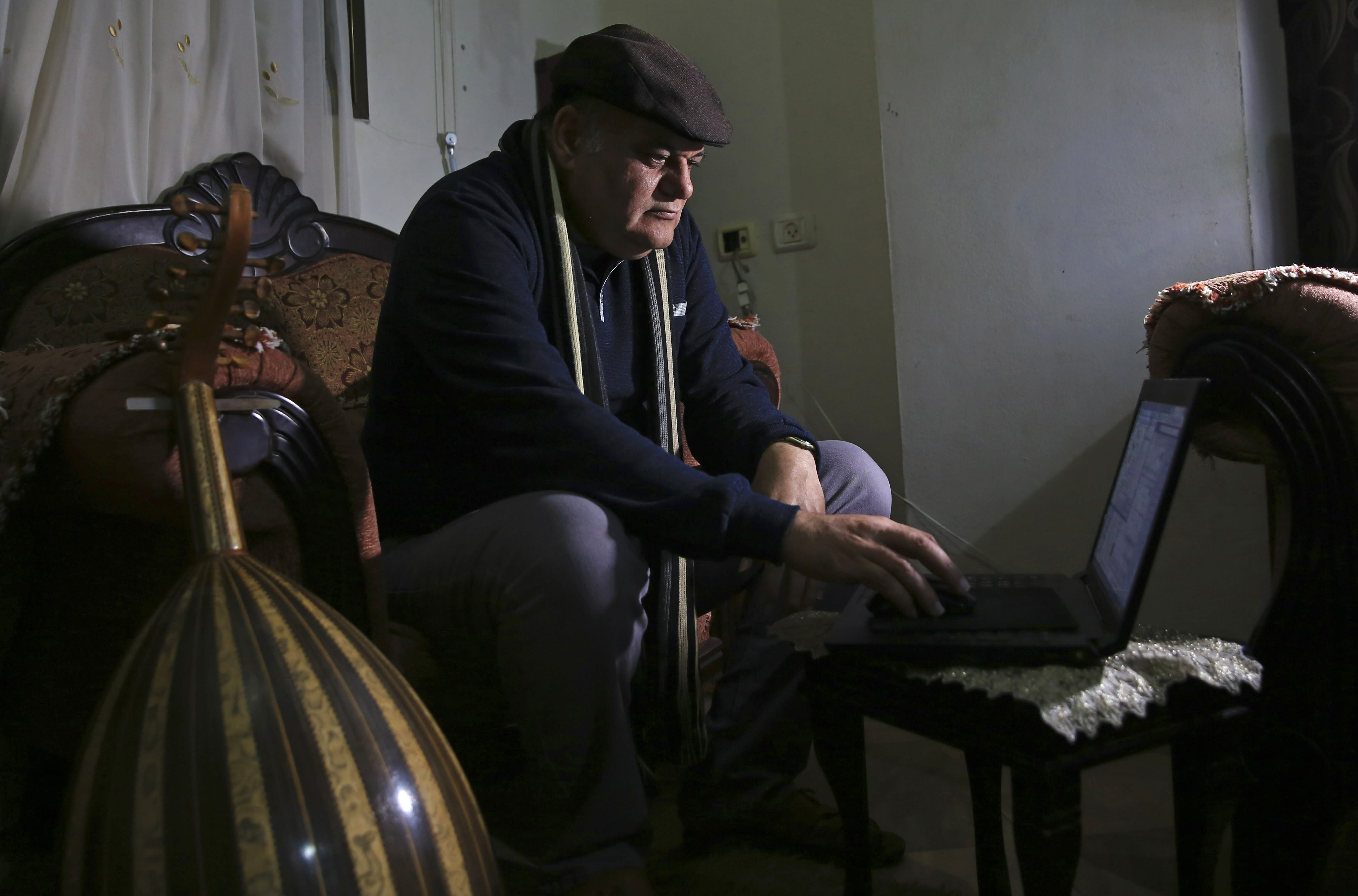 """In this Tuesday, Jan. 29, 2019 photo, Palestinian actor and playwright Ali Abu Yaseen, checks his laptop during an interview in his home at the Shati refugee camp in Gaza City. A new documentary called """"Gaza"""" is hitting the screens at the prestigious Sundance Film Festival this week, providing a colorful glimpse of life in the blockaded Hamas-ruled territory. But one of its main subjects, Abu Yaseen, won't be attending the gathering due to the very circumstances depicted in the film. (AP Photo/Adel Hana)"""