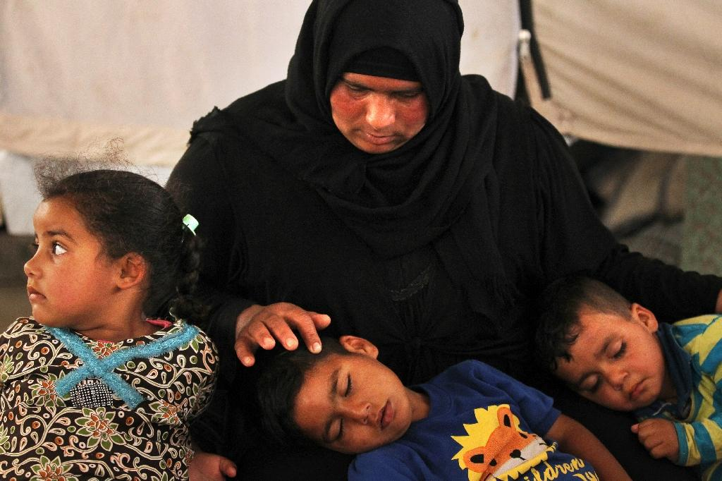 Salima, a 36-year-old mother of four living in the Laylan 2 displacement camp, sits with her children in their tent at the camp, southeast of Kirkuk in northern Iraq (AFP Photo/AHMAD AL-RUBAYE)