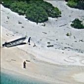A couple stranded on a remote Pacific island got rescued after the US Navy spotted their SOS message in the sand