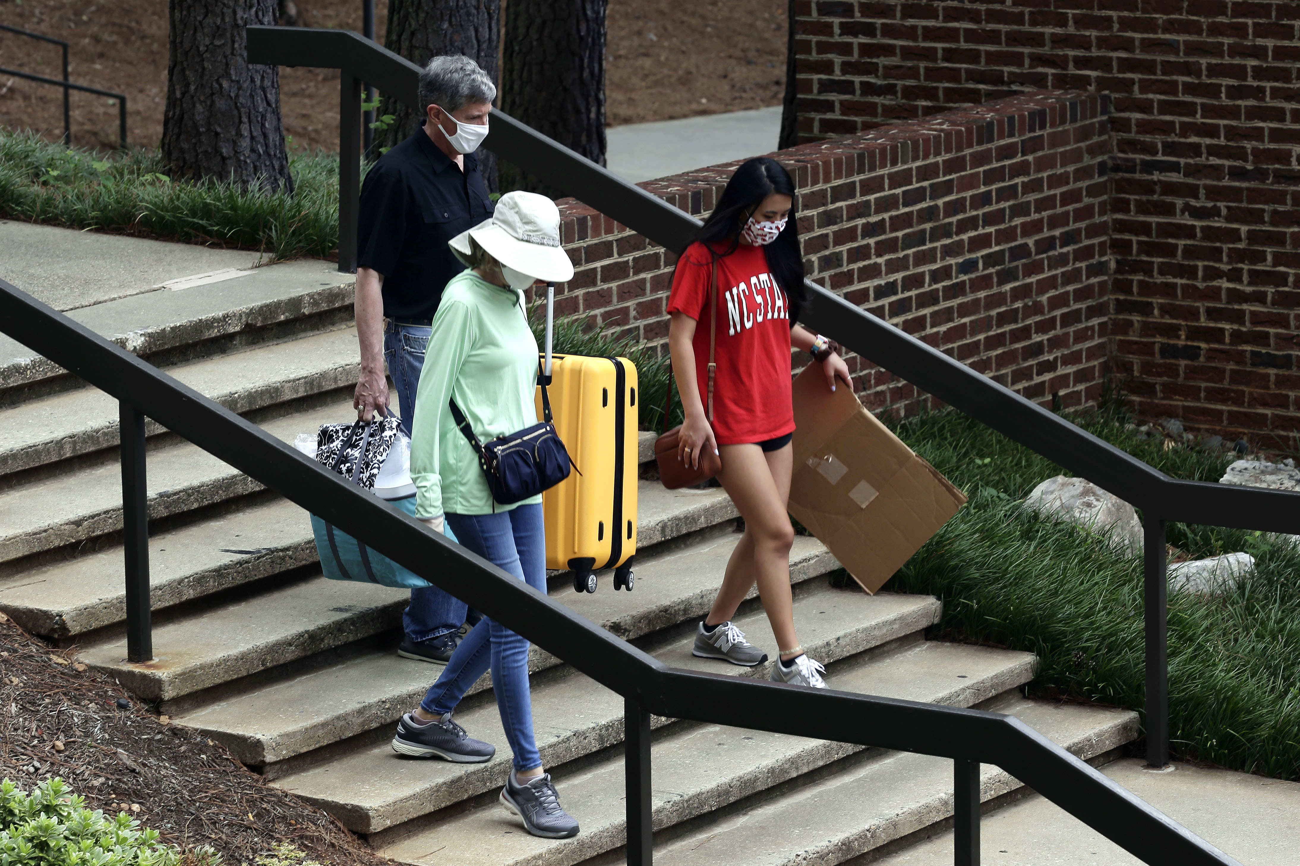 Charles Jacocks, rear, along with his wife Carrie and incoming freshman Ann Grace, right, carry their belongings as college students begin moving in for the fall semester at N.C. State University in Raleigh, N.C., Friday, July 31, 2020. The first wave of college students returning to their dorms aren't finding the typical mobs of students and parents. At N.C. State, the return of students was staggered over 10 days and students were greeted Friday by socially distant volunteers donning masks and face shields. (AP Photo/Gerry Broome)