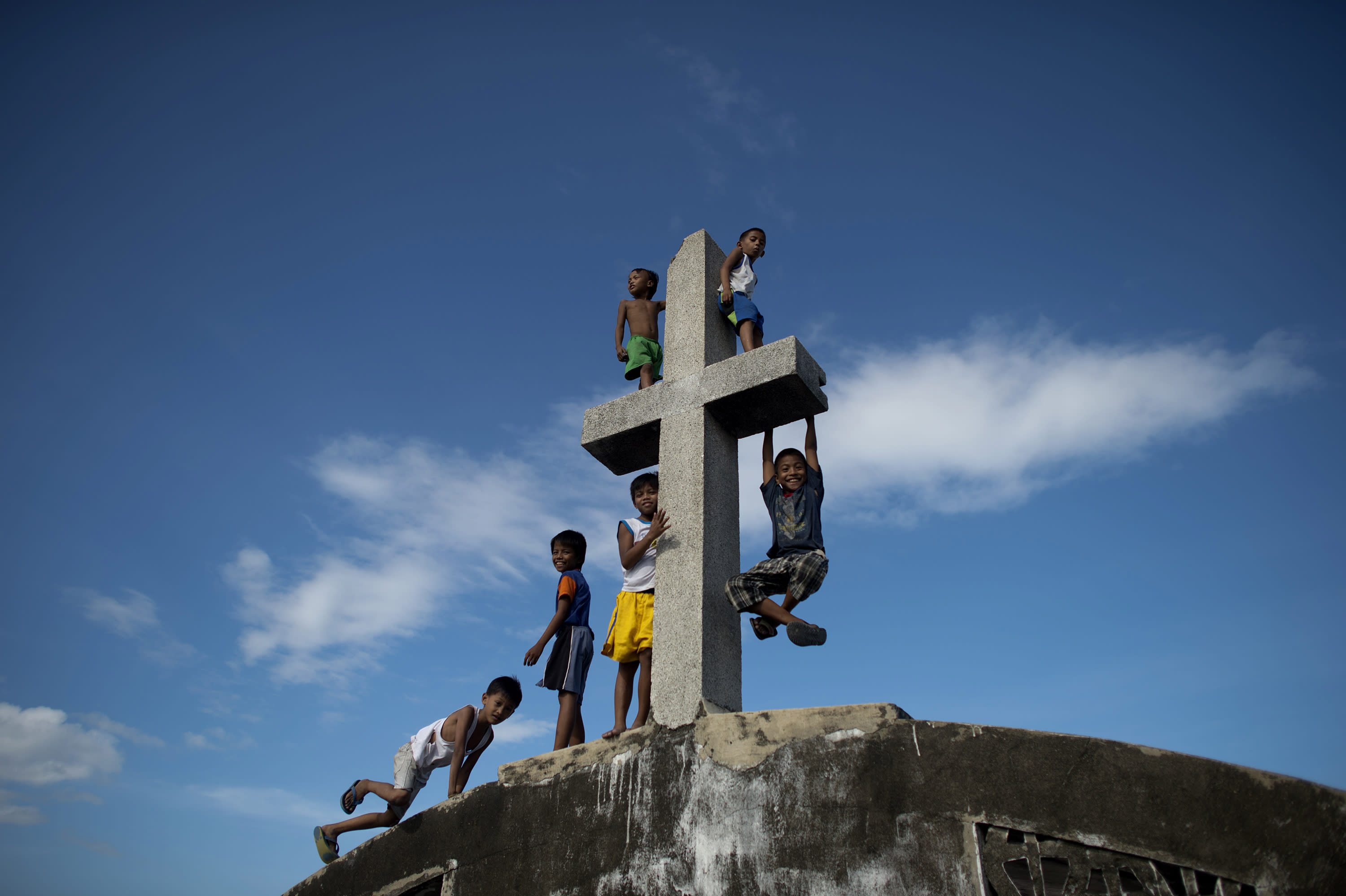 Local boys climb a cross at the Navotas Public Cemetery in Manila, on October 31, 2014 (AFP Photo/Noel Celis)