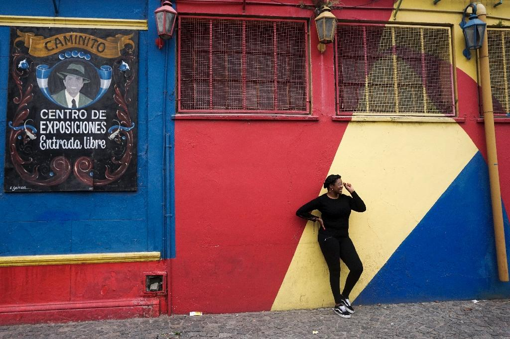 A tourist poses for pictures during a visit to the traditional street museum Caminito in La Boca neighbourhood in Buenos Aires (AFP Photo/Eitan ABRAMOVICH)