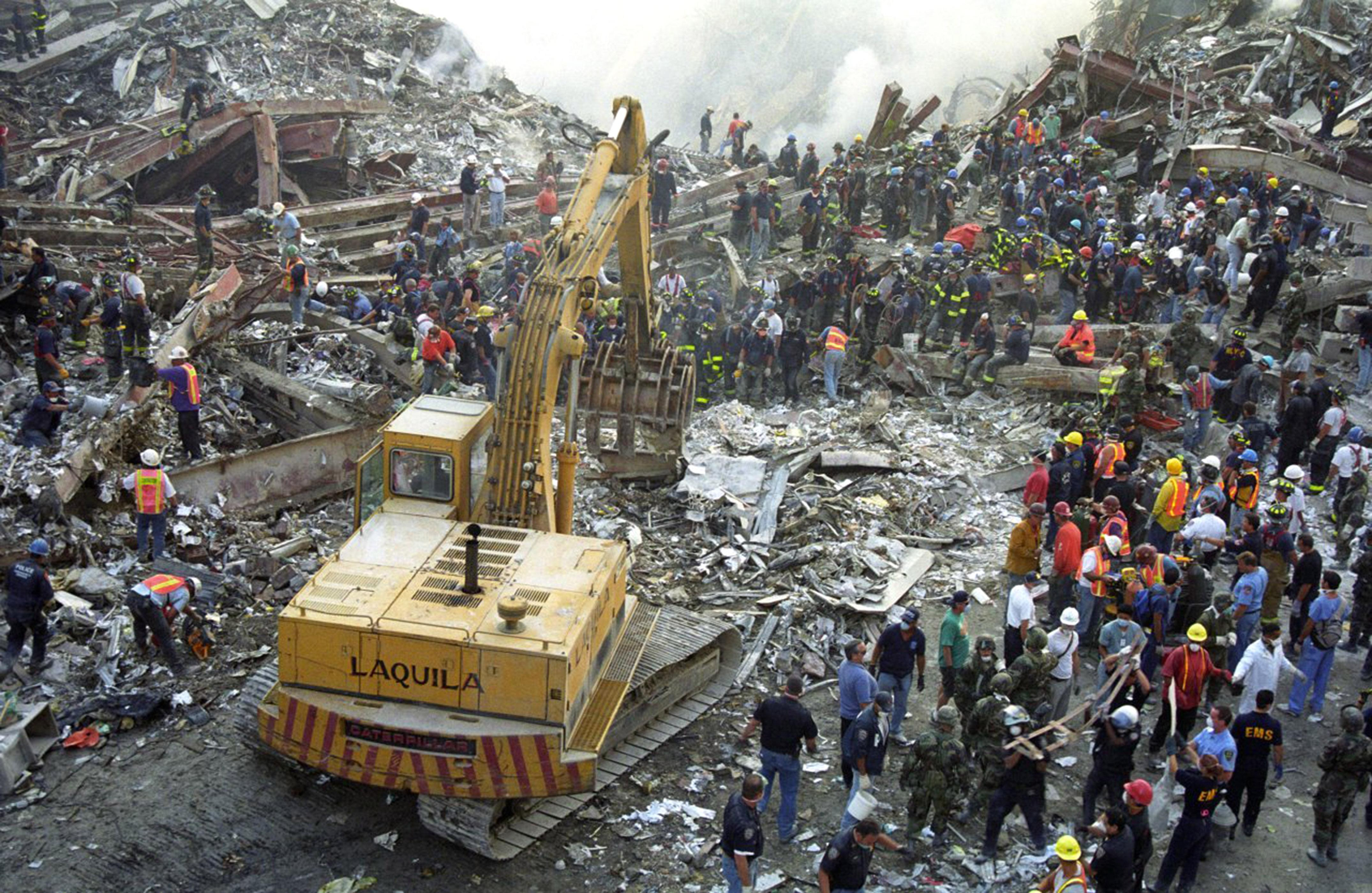 A digger clearing rubble as emergency services personell search for survivors. (Caters)