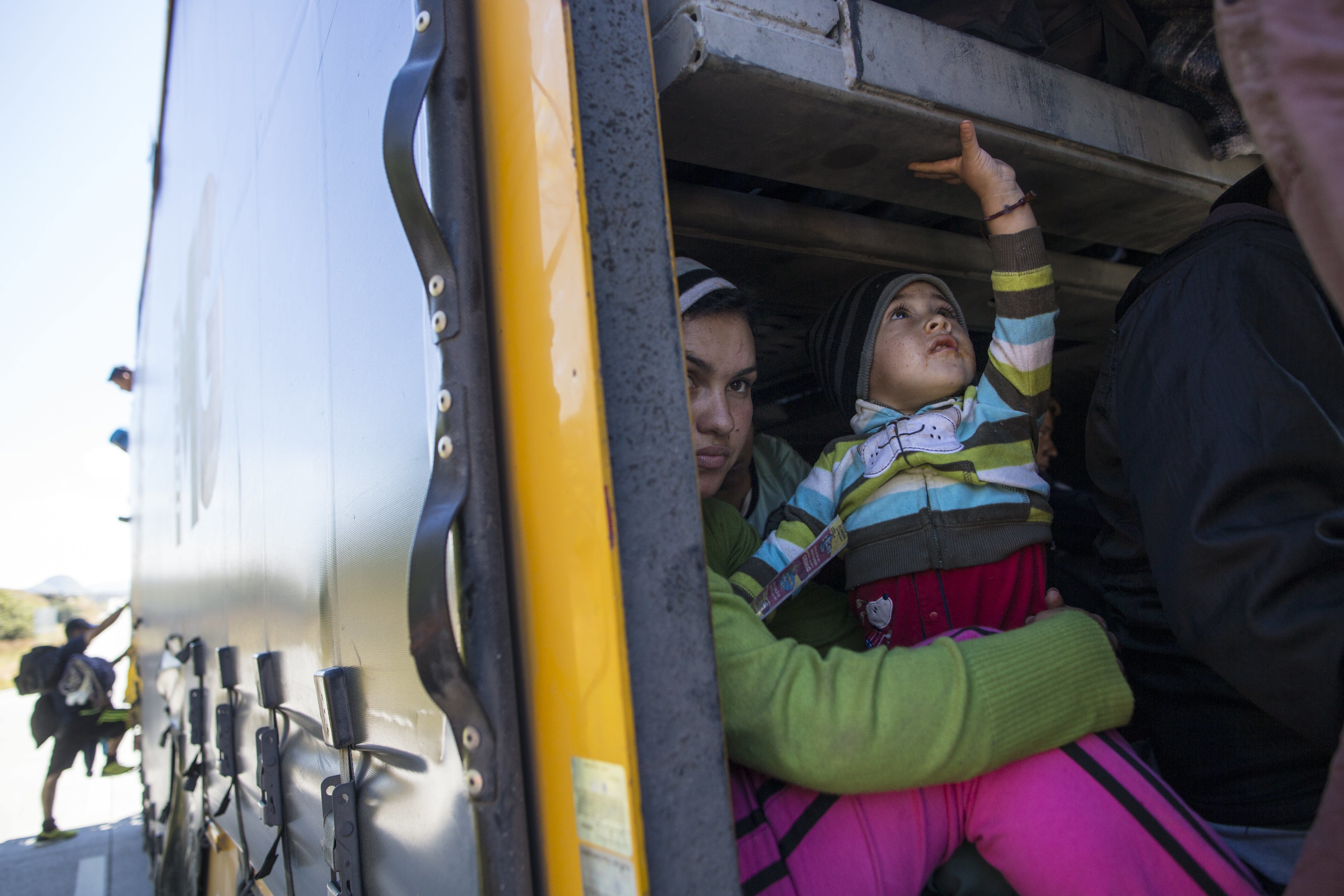 Honduran migrants Marta Esperanza and Reyes River travel in a truck with Marta's son Oscar Alejandro along the highway that connects Guadalajara with Tepic, Mexico, Tuesday, Nov. 13, 2018, as they travel with a migrant caravan. Many migrants say they are fleeing rampant poverty, gang violence and political instability primarily in the Central American countries of Honduras, Guatemala, El Salvador and Nicaragua. (AP Photo/Rodrigo Abd)