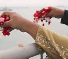 Relatives of plane's victims cast flowers into Indonesia sea