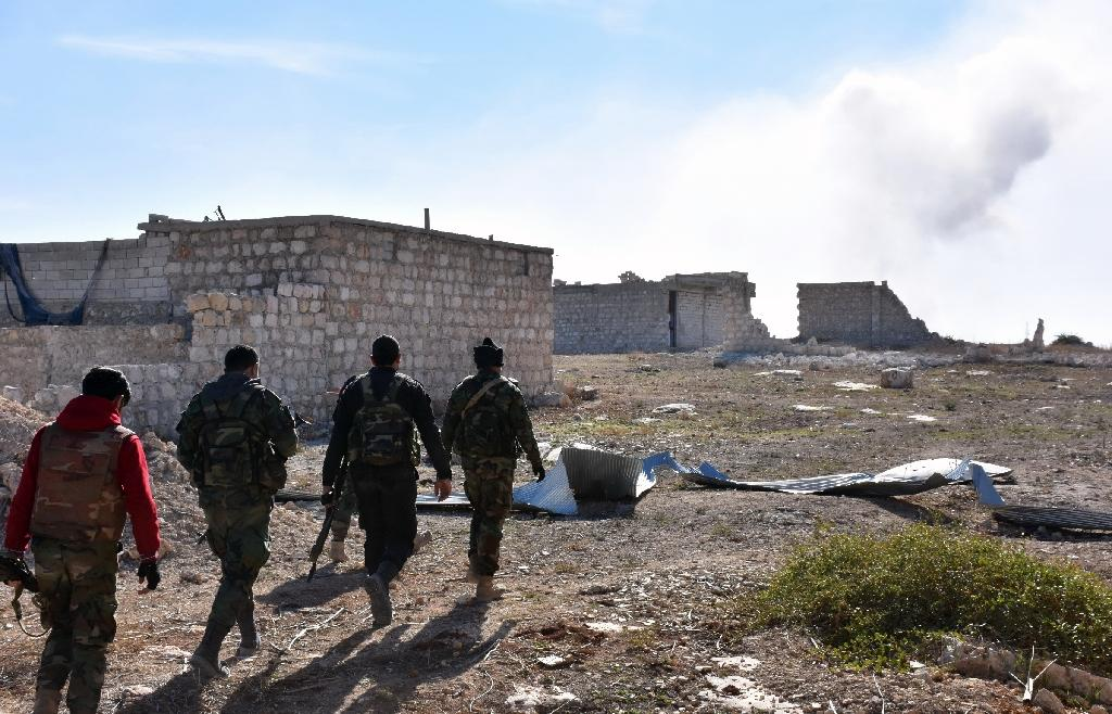 Syrian pro-government forces walk past damaged houses as they approach the Baeedin district in eastern Aleppo, near Masaken Hanano, on November 23, 2016 (AFP Photo/George Ourfalian)