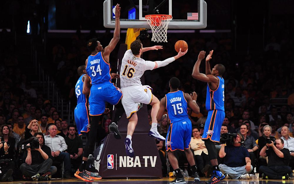 Pau Gasol of the Los Angeles Lakers (#16) drives to the hoop under from the Oklahoma City Thunder during their NBA matchup at Staples Center in Los Angeles, California on March 9, 2014