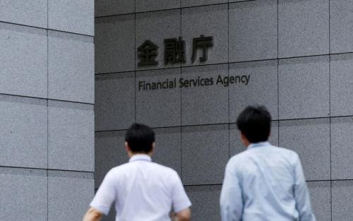 Men walk toward a sign of Japan's Financial Services Agency in Tokyo