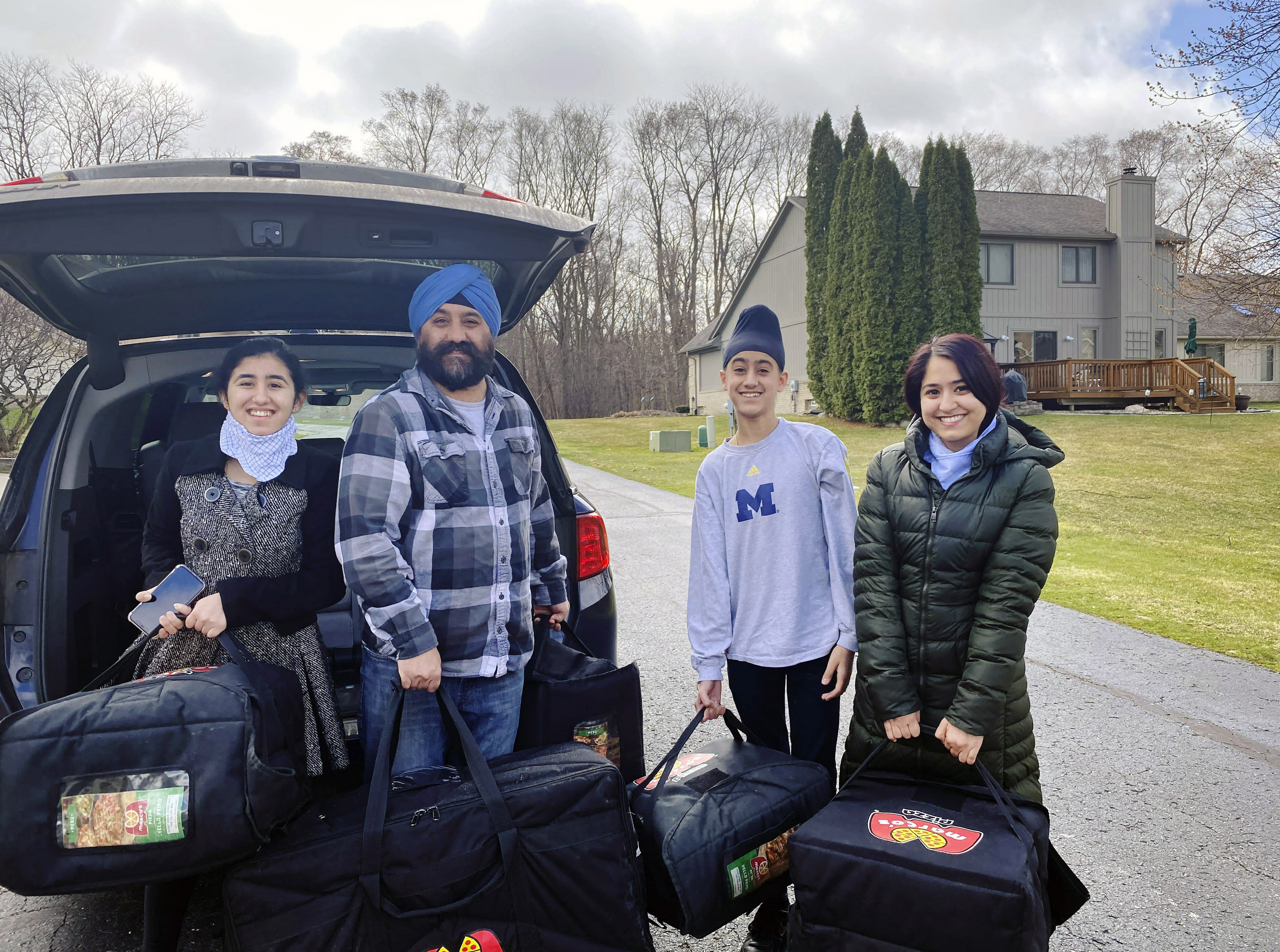 In this April 1, 2020 photo provided by Paramjyoti Kaur Singh, Singh family members Baani, Shalinder, Arjun and Jasveen Kaur pose for a photo before delivering pizzas to health care workers in Detroit. (Paramjyoti Kaur Singh via AP)