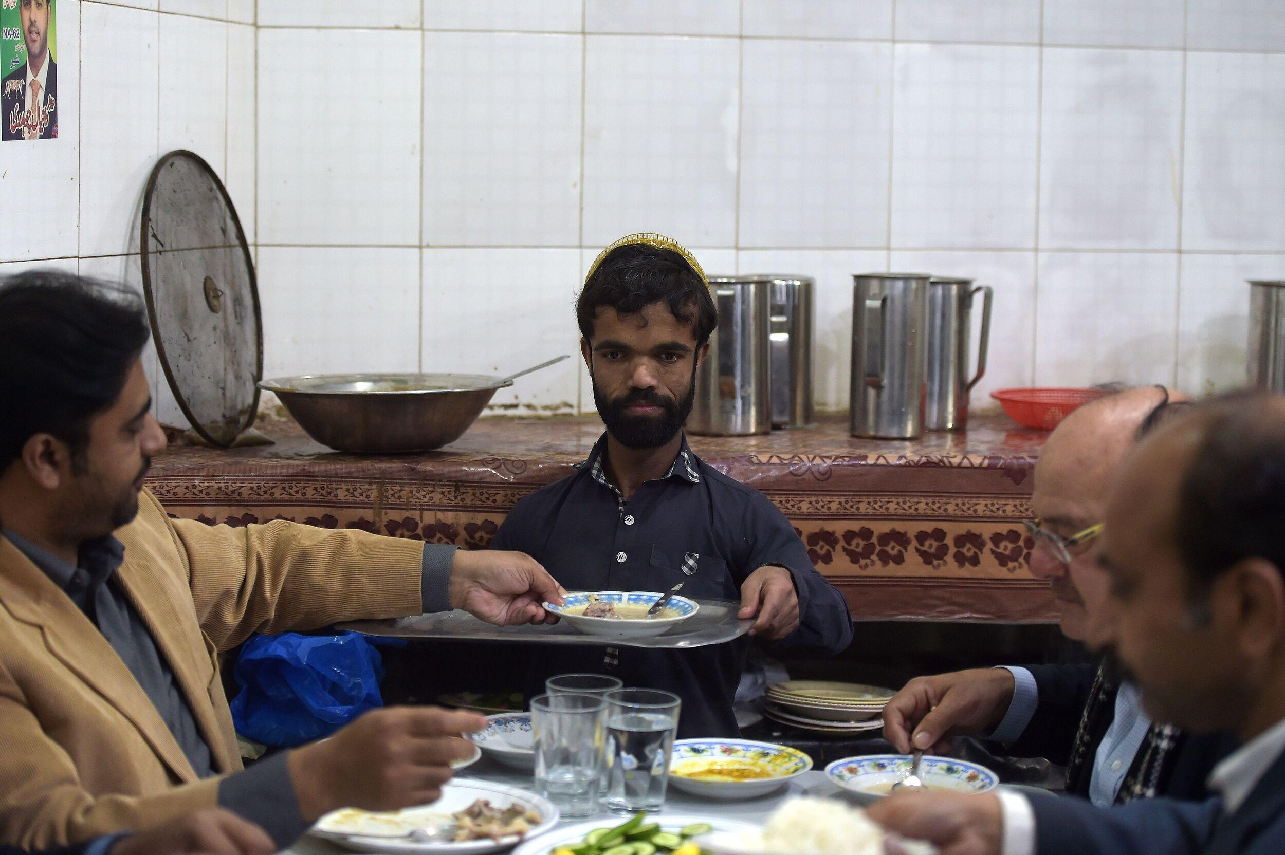 In this picture taken on February 22, 2019, Rozi Khan (C), a 25-year-old Pakistani waiter who resembles US actor Peter Dinklage, serves food to customers at Dilbar Hotel in Rawalpindi. - Rozi Khan had never heard of the Game of Thrones -- or its hugely popular character Tyrion Lannister -- until his striking resemblance to the dwarf anti-hero got heads turning at home. (Photo by AAMIR QURESHI / AFP) / To go with PAKISTAN-LIFESTYLE-TELEVISION-ENTERTAINMENT (Photo credit should read AAMIR QURESHI/AFP/Getty Images)