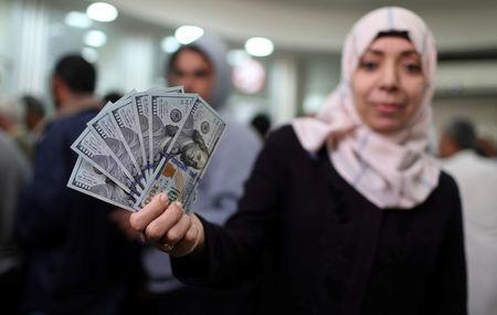 A Palestinian Hamas-hired employee displays US dollar notes after receiving her salary, in the southern Gaza Strip November 9, 2018. REUTERS/Ibraheem Abu Mustafa
