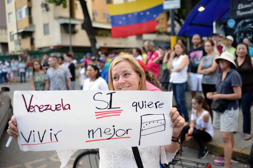 """Venezuela wants to live better"" -- voters celebrate in Caracas after taking part in an opposition-organized ballot challenging embattled Venezuelan President Nicolas Maduro's plan to rewrite the constitution (AFP Photo/FEDERICO PARRA )"