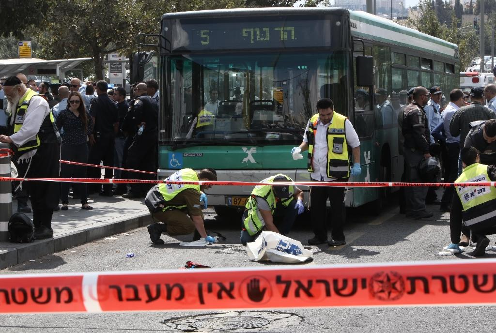 Israeli Zaka volunteers clean up blood stains at site where a 19-year-old Palestinian man stabbed a Jewish man in Jerusalem on October 8, 2015 (AFP Photo/Gali Tibbon)